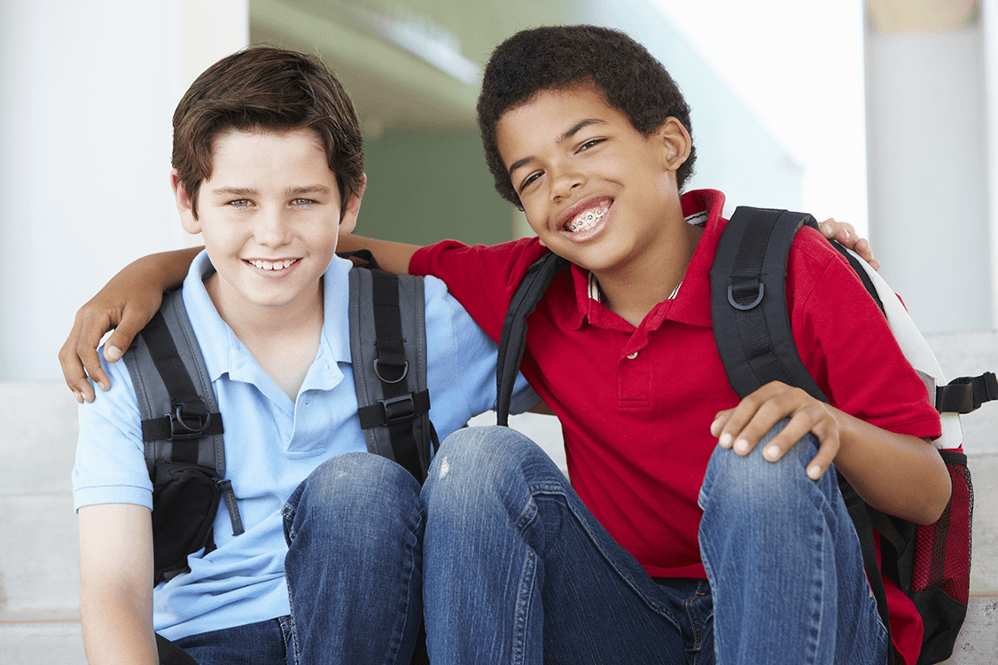 two kids with backpacks and braces